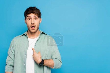 Photo pour Surpris jeune homme pointant du doigt lui-même isolé sur bleu - image libre de droit
