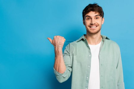 Photo for Happy young man pointing with thumb while looking at camera on blue - Royalty Free Image