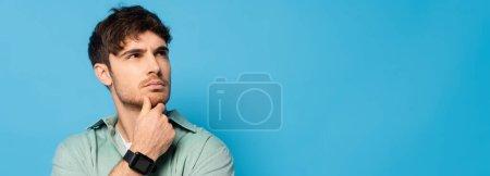 Photo pour Image horizontale d'un homme réfléchi touchant le menton tout en regardant loin isolé sur le bleu - image libre de droit