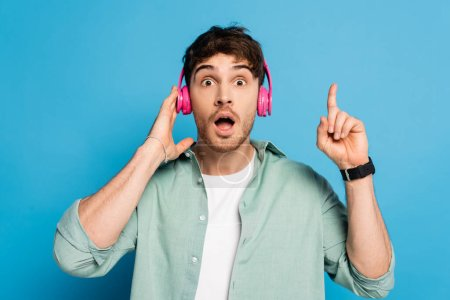 Photo for Shocked young man touching wireless headphones and showing idea gesture on blue - Royalty Free Image