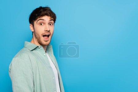 Photo pour Choqué jeune homme avec bouche ouverte regardant caméra isolée sur bleu - image libre de droit