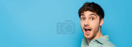 Photo for Horizontal image of excited young man looking at camera isolated on blue - Royalty Free Image