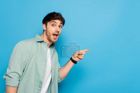 Photo pour Choqué jeune homme regardant caméra et pointant du doigt sur bleu - image libre de droit