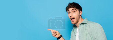 horizontal image of excited young man pointing with finger and looking at camera on blue