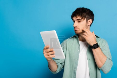 Photo for Thoughtful young man touching face while looking at digital tablet on blue - Royalty Free Image