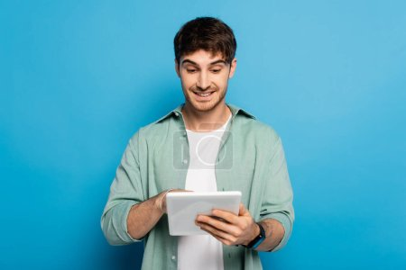 happy young man using digital tablet on blue