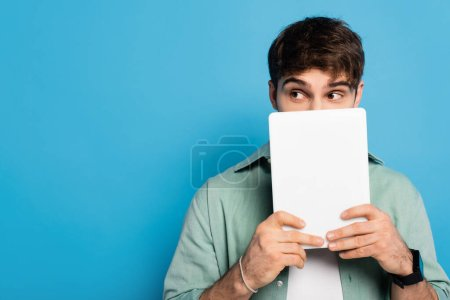 scared young man obscuring face with digital tablet on blue