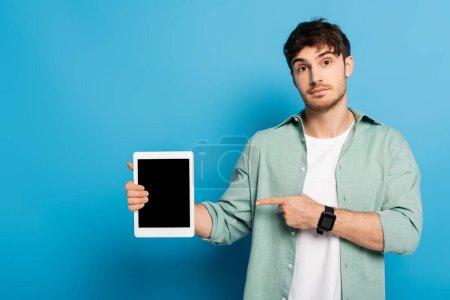 joven guapo apuntando con el dedo a la tableta digital con pantalla en blanco en azul