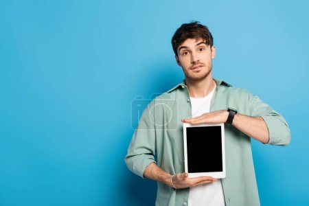 Photo for Handsome young man showing digital tablet with blank screen on blue - Royalty Free Image