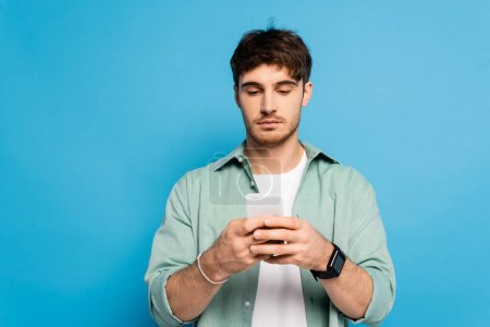 serious young man chatting on smartphone isolated on blue