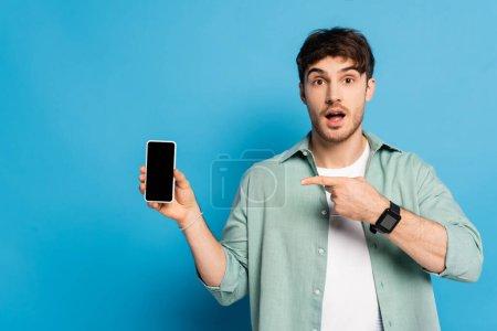Photo pour Surpris jeune homme pointant vers smartphone avec écran blanc sur bleu - image libre de droit