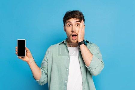 Photo pour Choqué jeune homme touchant le visage et montrant smartphone avec écran blanc sur bleu - image libre de droit