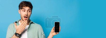 Photo pour Image horizontale d'un jeune homme choqué montrant un smartphone avec écran blanc sur fond bleu - image libre de droit