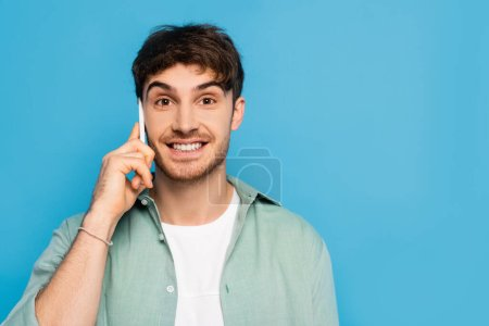 Photo for Happy young man talking on smartphone while looking at camera isolated on blue - Royalty Free Image