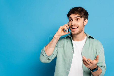 cheerful young man talking on smartphone while standing with open arm on blue