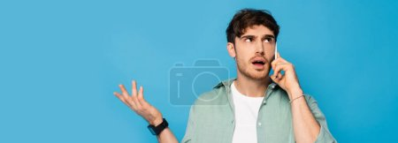 Photo pour Image horizontale d'un jeune homme confus montrant un geste d'haussement d'épaules tout en parlant sur smartphone isolé sur bleu - image libre de droit