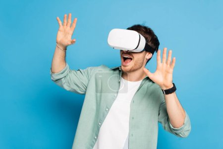 Photo for Excited young man gesturing while using vr headset on blue - Royalty Free Image