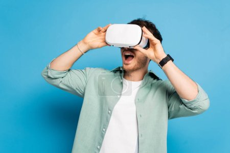 Photo for Excited young man using vr headset on blue - Royalty Free Image