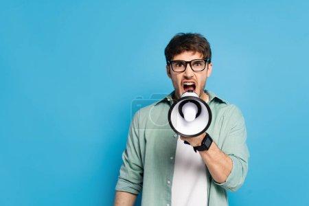 Photo pour Jeune homme en colère criant dans le mégaphone tout en regardant la caméra sur bleu - image libre de droit