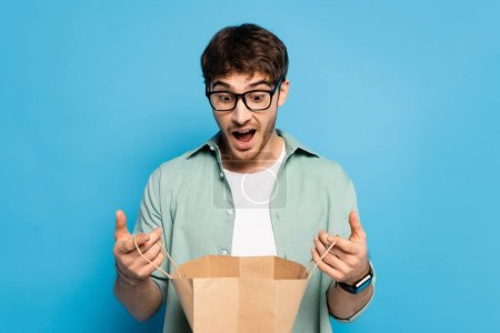 Photo for Surprised young man looking into shopping bag on blue - Royalty Free Image