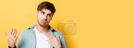 Photo pour Jeune homme épuisé touchant chemise et main en agitant tout en souffrant de chaleur sur jaune - image libre de droit