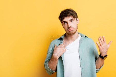 Photo pour Jeune homme mécontent touchant chemise et agitant la main tout en souffrant de chaleur sur jaune - image libre de droit