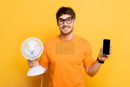 happy young man holding electric fan and smartphone with blank screen on yellow
