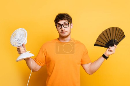 Photo for Discouraged young man holding electric and hand fans while looking at camera on yellow - Royalty Free Image