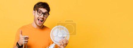 Photo pour Homme excité dans des lunettes tenant sac à provisions avec un nouveau ventilateur électrique sur jaune, en-tête de site Web - image libre de droit