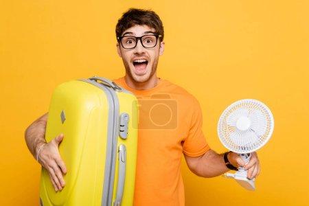 Photo pour Excité homme tenant sac de voyage et ventilateur électrique sur jaune - image libre de droit