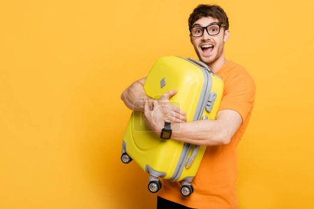 Photo for Excited male tourist holding suitcase for summer vacation on yellow - Royalty Free Image