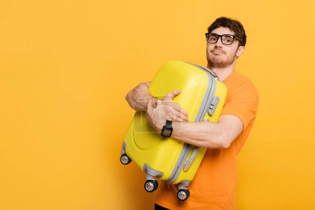 Photo for Funny male tourist holding suitcase for summer vacation on yellow - Royalty Free Image