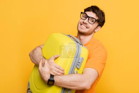 Photo for Happy male tourist holding suitcase for summer vacation isolated on yellow - Royalty Free Image