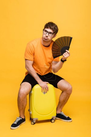 confused man suffering from heat while using hand fan and sitting on suitcase on yellow