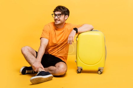 Photo for Happy tourist sitting near travel bag for summer vacation on yellow - Royalty Free Image