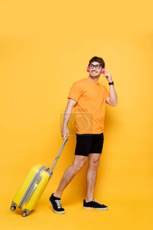 Photo for Happy handsome man in headphones walking with travel bag on yellow - Royalty Free Image