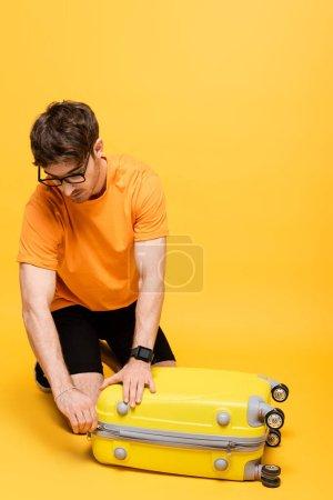 Photo pour Jeune mâle valise d'emballage touristique pour les vacances d'été sur jaune - image libre de droit