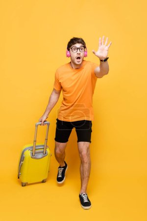 Photo pour Homme criant tard dans les écouteurs en cours d'exécution avec sac de voyage sur jaune - image libre de droit
