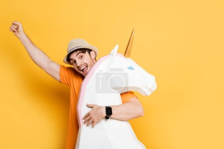 Photo for Excited man in summer hat holding fist up and hugging decorative unicorn on yellow - Royalty Free Image