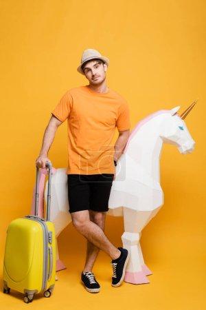 Photo pour Jeune voyageur masculin en chapeau debout avec licorne et valise sur jaune - image libre de droit