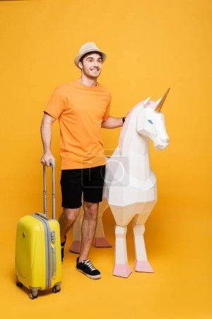 Photo pour Voyageur souriant en chapeau debout avec licorne et valise sur jaune - image libre de droit