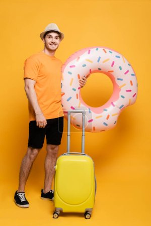 Photo for Happy man in hat with suitcase and inflatable donut ready for summer vacation on yellow - Royalty Free Image