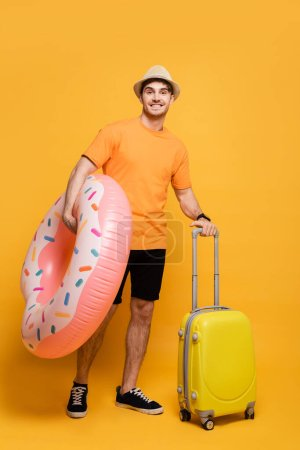 Photo for Smiling man with suitcase and inflatable donut ready for summer vacation on yellow - Royalty Free Image