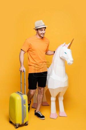 Photo pour Voyageur joyeux en chapeau debout avec licorne et valise sur jaune - image libre de droit