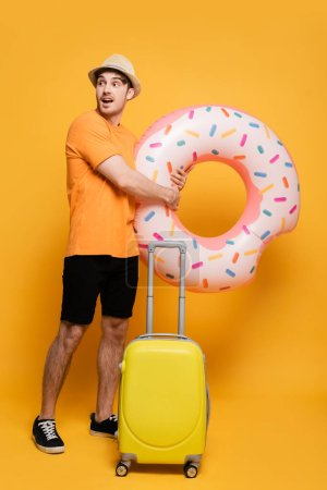 Photo for Young excited man with suitcase and inflatable donut ready for summer vacation on yellow - Royalty Free Image