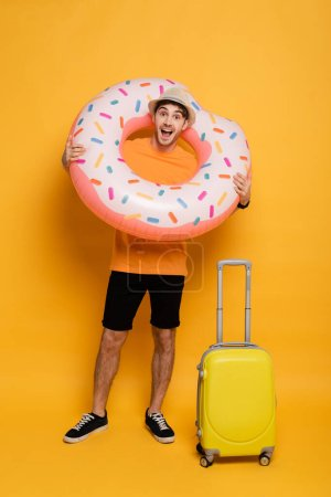 Photo for Excited man with suitcase and inflatable donut ready for summer vacation on yellow - Royalty Free Image