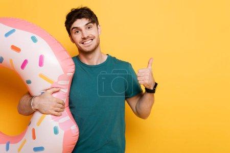 Photo pour Homme souriant montrant pouce levé tout en se tenant debout avec beignet gonflable sur jaune - image libre de droit