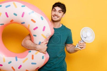 Photo pour Homme souriant tenant donut gonflable et petit ventilateur électrique sur jaune - image libre de droit