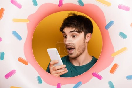 Photo for Surprised young man with inflatable donut using smartphone on yellow - Royalty Free Image