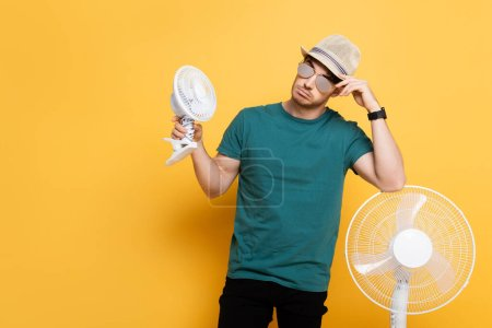 Photo for Young man in sunglasses and hat standing with two electric fans on yellow - Royalty Free Image
